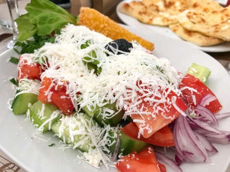 Greek salad is made with pieces of tomatoes, sliced cucumbers, onion, feta cheese, and olives, typically seasoned with salt and greek mountain oregano, and dressed with olive oil.