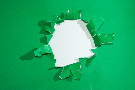 penetraci�n: Round hole in green paper on white background inside