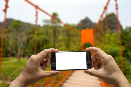 Use mobile smartphone. Shot with one-person view, blank screen on red bridge.