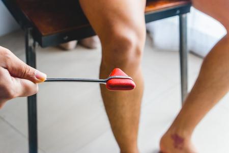 Médecin testant le réflexe rotulien ou réflexe du genou avec le jerk hummer rouge sur le genou du jeune homme.