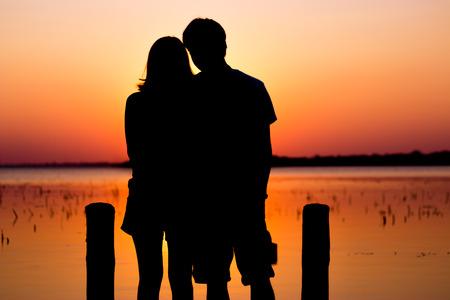 La luna de miel de ensueño en Tailandia. La silueta de la pareja romántica en el lago buriram. Foto de archivo