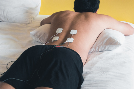 Patient applying electrical stimulation therapy on back. Electrical tens.