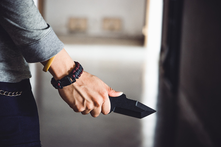 Closeup of a young man hand, holding a knife, about to attack over dark background. Imagens