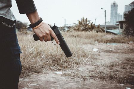 Tueur tenant une arme à côté de lui, plan recadré d'un homme tenant une arme à la main. Banque d'images