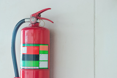 Fire extinguisher on the white cement wall background. Imagens