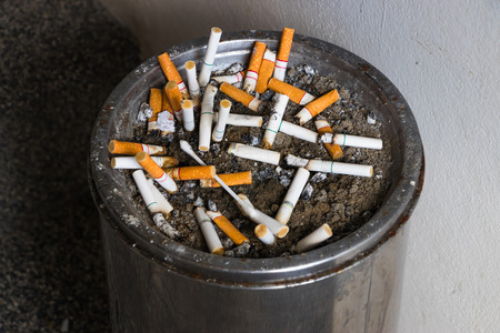 The cigarette butts in ashtray with sand at smoking.