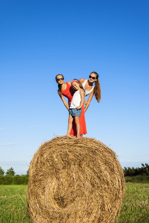 children on a bale of straw photo