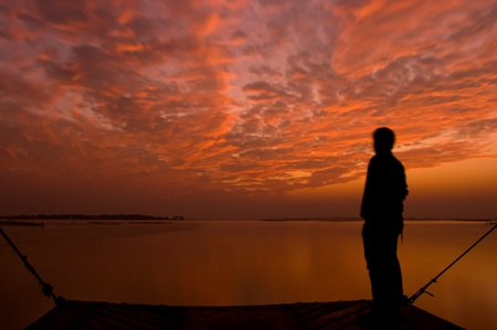 chilika: Silhouette of a man with dramatic sky and clouds in Chilika, India