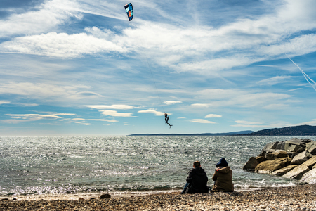 people watching a kite surfer in action on french riviera in saint raphael, france