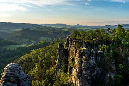 view on sandstone rocks and mountains at sunrise from trail to bastion bridge in saxon switzerland, germany