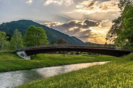 Brücke bei Sonnenuntergang am Ufer der Ammer in Oberammergau, Deutschland Standard-Bild