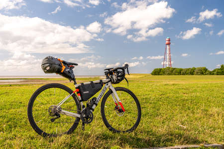 bikepacking at the north sea, view on the lighthouse of camping near emden with a packed gravel bike in front, north sea, germany