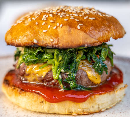 cheeseburger with beef patty, spinach, red sauce, cheddar cheese piled up in a self-made bun with sesame