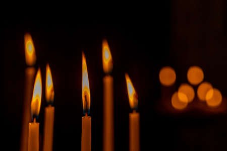 closeup of multiple burning candles with beautiful bokeh in church Archivio Fotografico