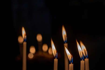 closeup of multiple burning candles with beautiful bokeh in church