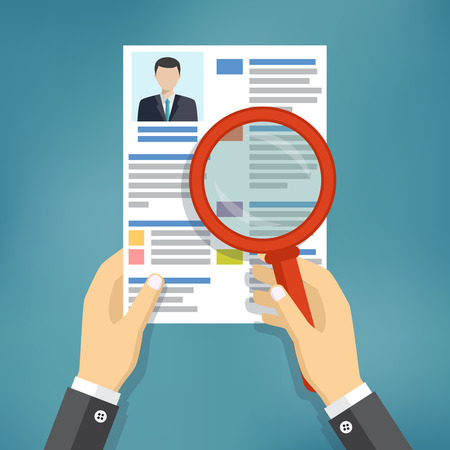 Hands holding a resume and learn it through a magnifying glass, the employer is considering job candidates resume. business concept job interview