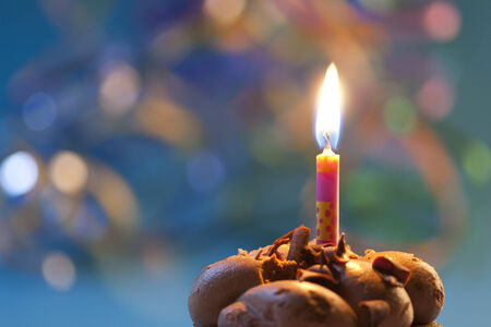 Birthday cupcake with candle  Colorful blurry background