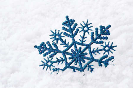 Shiny blue snowflake on snow