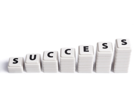 Stacked white squared pieces forming the word success on white  Stock Photo
