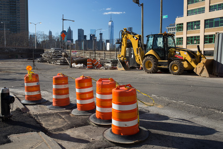 Brooklyn, New York - USA - July 10 2016: Construction site with orange cones and backhoe with world trade center and new york skyline in background