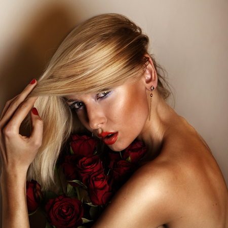 Beauty portrait of attractive blonde woman looking at camera holding bouquet roses. photo