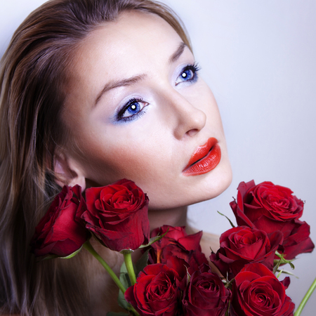 Portrait od beautiful sensual woman with red roses.