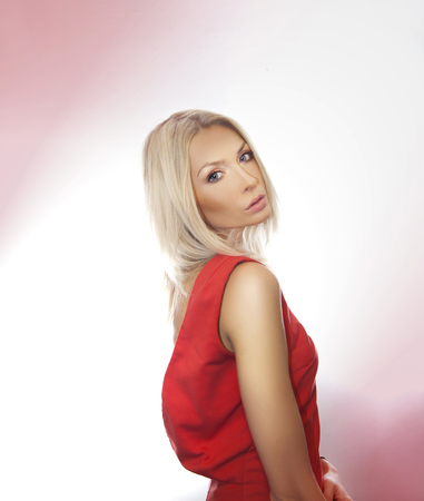 Sensual blonde beautiful woman posing wearing red dress, looking at camera. photo