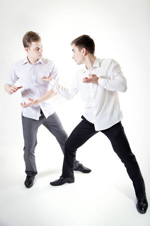 Two young hansome businessmen fighting. Studio shot. Stock Photo