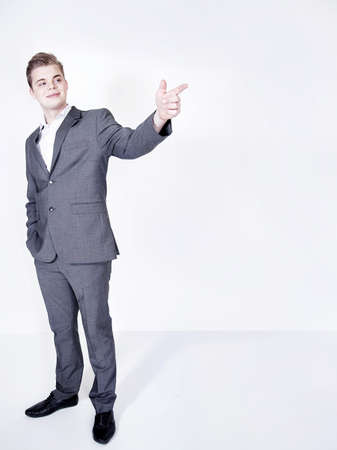 hansome: Young hansome businessman posing, showing something. Studio shot. Stock Photo