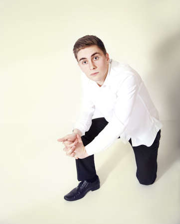Successful young business man looking at camera, kneeling. photo