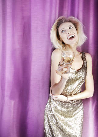 Smiling beautiful blonde woman wearing elegant gold dress, drinking wine, celebrating. photo