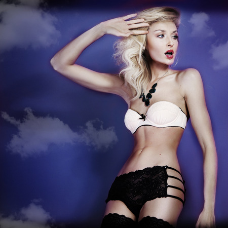 light blue lingerie: Slim beautiful pretty blonde woman posing in sexy lingerie over clouds.  Stock Photo
