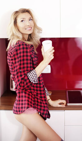 Beautiful young blonde woman holding cup of coffee in kitchen, smiling, looking at camera. photo