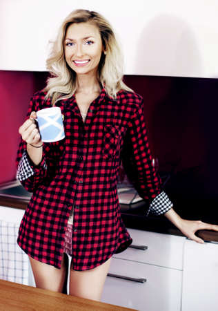 Beautiful young blonde woman holding cup of tea in kitchen, smiling, looking at camera. photo