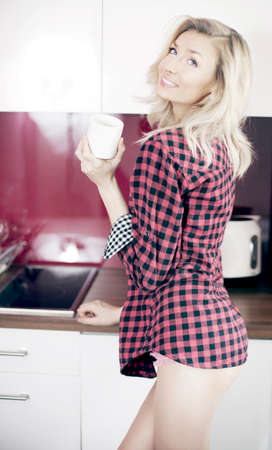 Beautiful young blonde woman holding cup of coffee in kitchen, smiling. photo