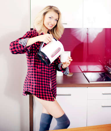 Beautiful young blonde woman making tea, smiling, looking at camera. photo