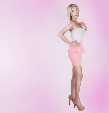 Fashionable beautiful blonde young woman posing in studio on pink background. photo