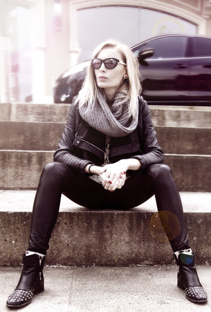 Fashionable blonde young woman in sunglasses sitting  Car on background  photo