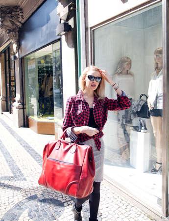 Fashionable young beautiful blonde woman walking on street, shopping  photo