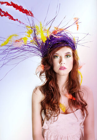 Colorful portrait of attractive woman with feathers and headgear looking at camera. photo