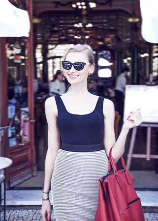 Fashionable smiling blonde beautiful woman walking on street, wearing sunglasses and holding big red bag. photo