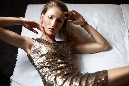 Sensual beautiful blonde woman posing, wearing gold fashionable dress, looking at camera.  photo