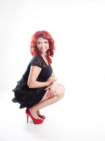 Adult beautiful redhead woman posing over white background. photo