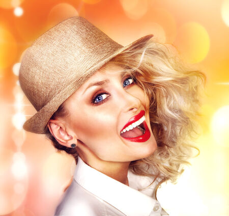 Portrait of beautiful smiling blonde woman looking at camera, wearing fashionable hat.