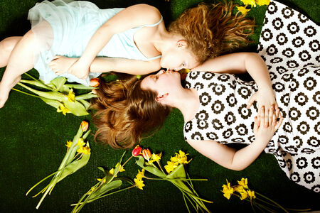 Two pretty young sisters lying over colorful flowers, kissing. Childrens day. Happy family. photo