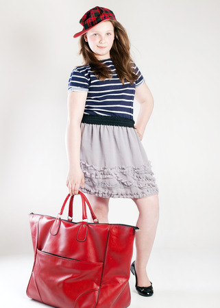 Young pretty teenager girl posing with fashionable red bag, looking at camera. Studio shot. Stock Photo - 28438640