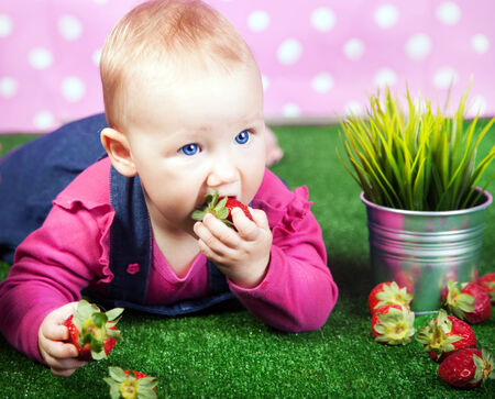 Small cute baby girl lying on grass, posing with strawberries. photo