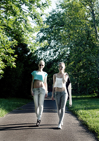 Happy two best friends walking in park. Summer sunny day. Fashionable girls smiling. photo