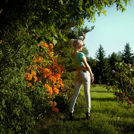 Sexy blonde woman posing over flowers on sunny day wearing fashionable clothes and sunglasses. Girl with slim perfect body. photo