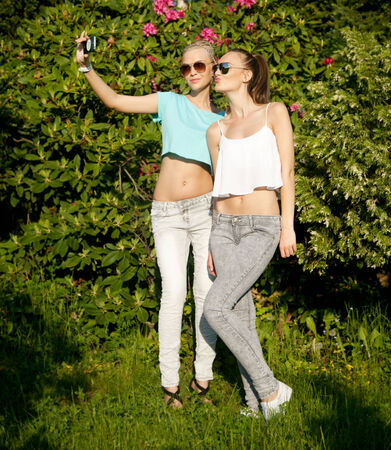 Two beautiful young girls posing, doing selfie outdoor in summer sunny day.  photo